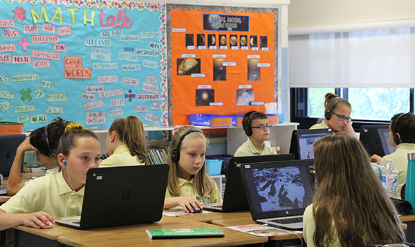 Fifth Graders use Chromebooks